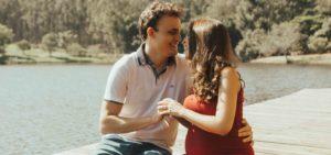 casal grávido sentado de mão dada