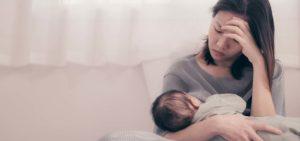 mãe deprimida com bebé ao colo