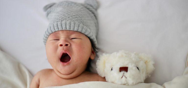 bebé deitado a bocejar com peluche