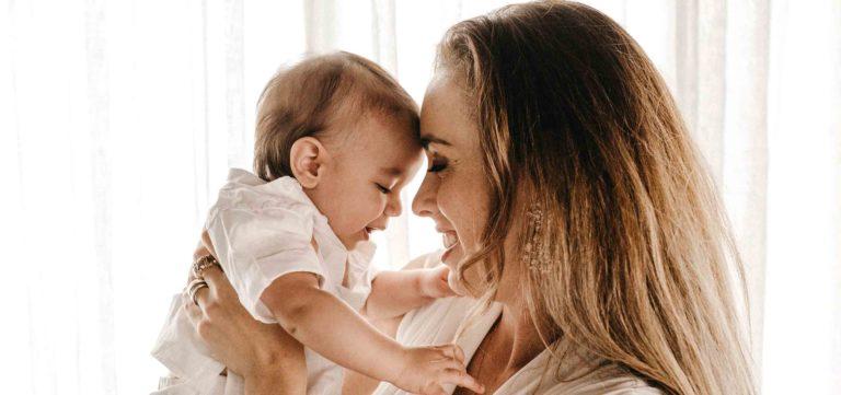 mãe com bebé ao colo com a cabeça enconstada