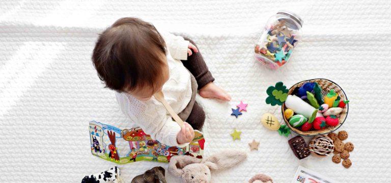 bebé a brincar no chão com vários brinquedos