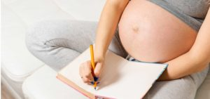grávida a apontar nomes de bebés num caderno