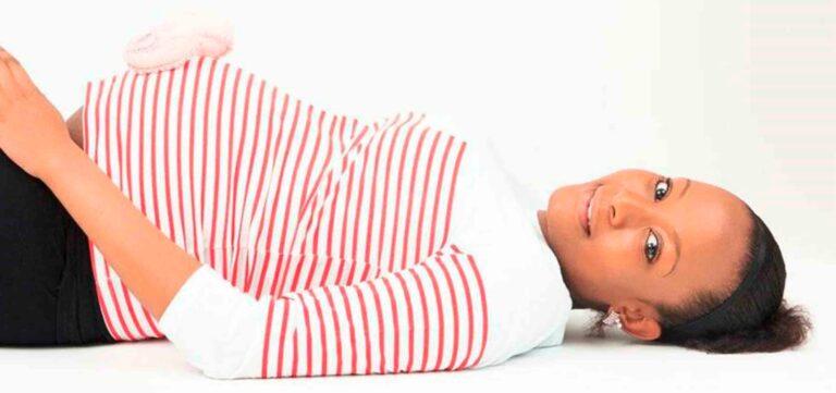 gravida no terceiro trimestre deitada com as mãos na barriga
